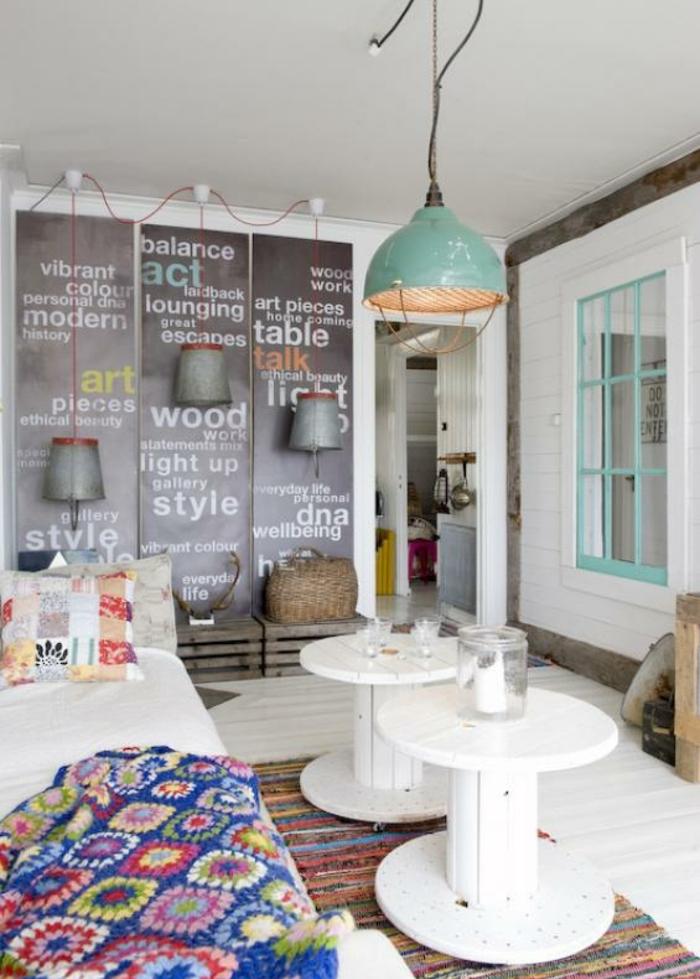 idée comment décorer un salon vintage industriel, canapé blanc, couverture à motifs floraux et tapis à rayures multicolores, coussins colorés, suspension industrielle, poster decoratif artistique, rangement cagette de bois
