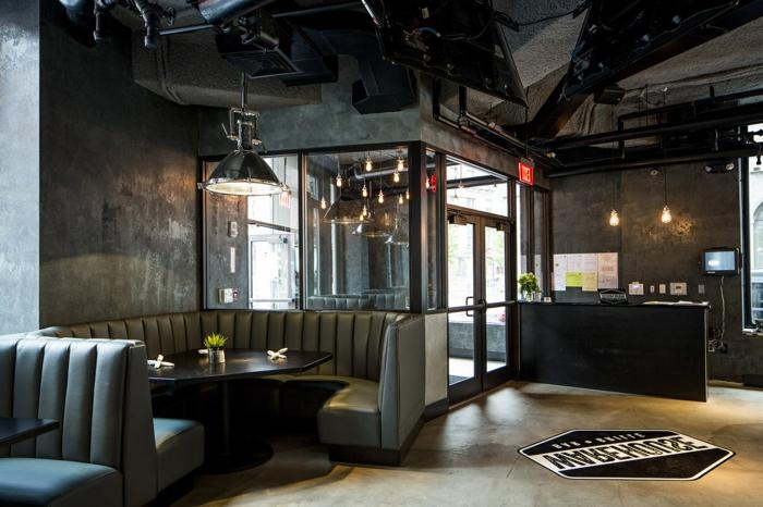 meuble industriel, mur en béton, lampe suspendue, canapé en cuir, table asymétrique noire, plancher gris