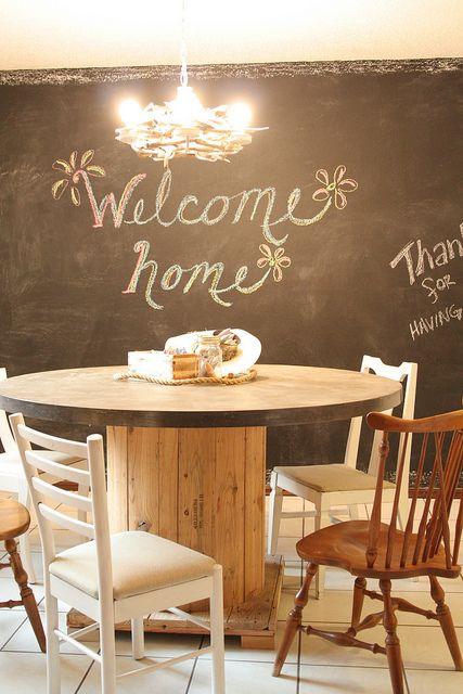 idée déco salle à manger, table en touret bois brut, chaises en bois, mur tableau noir, lustre intéressant, ambiance vintage chic