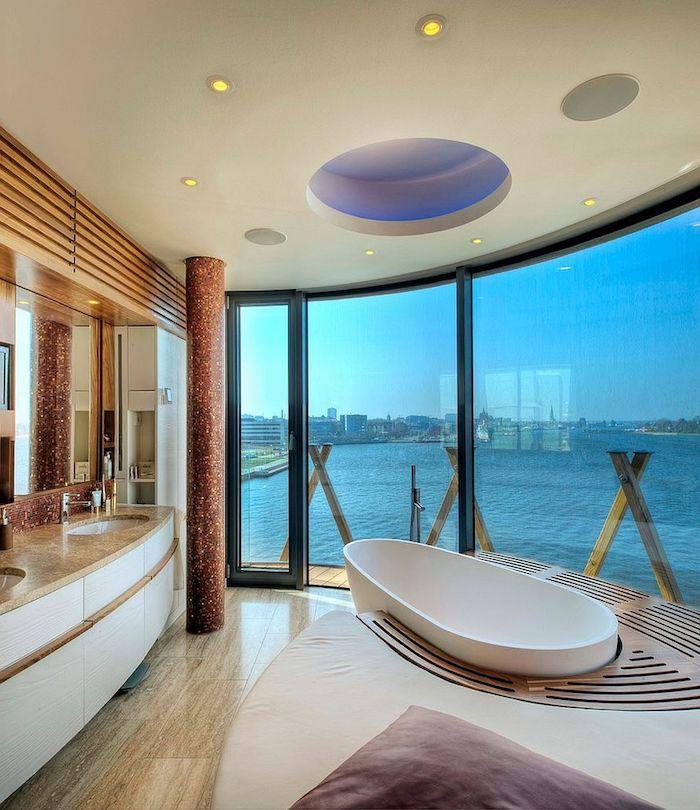 meubles salle de bain, comptoir beige, dallage imitation bois, coussin violet, vue sur la mer, robinet en acier