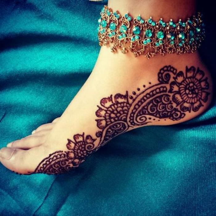 dessin henné, motifs végétaux dessinés sur le pied, bracelet avec pierres bleues