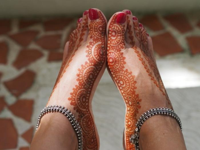 dessin henne, figures tatouées au henné orange, bracelets de cheville en argent