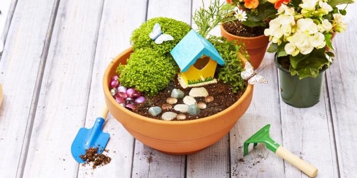 idée comment fabriquer un jardin de fée dans un pot de fleur en terre cuite, terreau, galets, plantes maisonnette, activités manuelles pour enfants printemps été