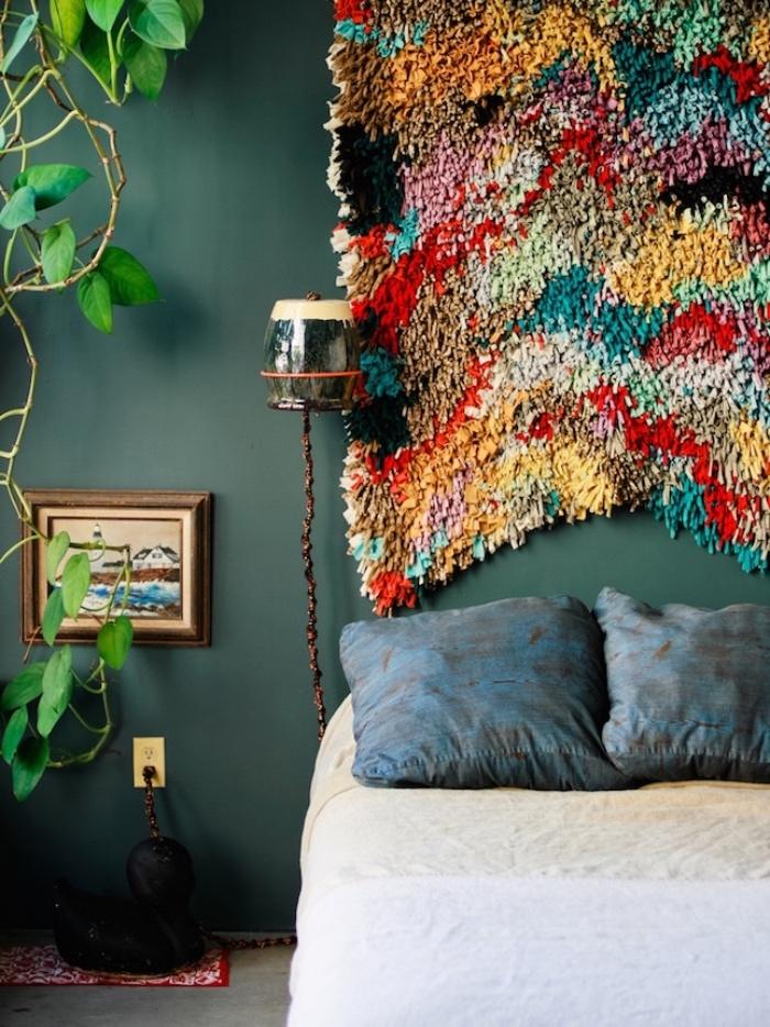 tete de lit a faire soi meme en tapis multicolore, mur couleur ver émeraude, coussins bleus et linge de lit blanc, plante verte