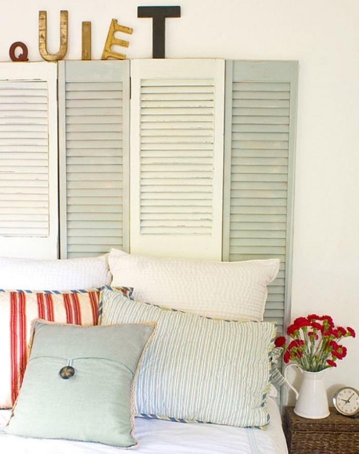 idée comment fabriquer une tete de lit en volets de porte en bois, couleur blanche vert clair pastel, coussins multicolores, table de nuit coffret en rotin