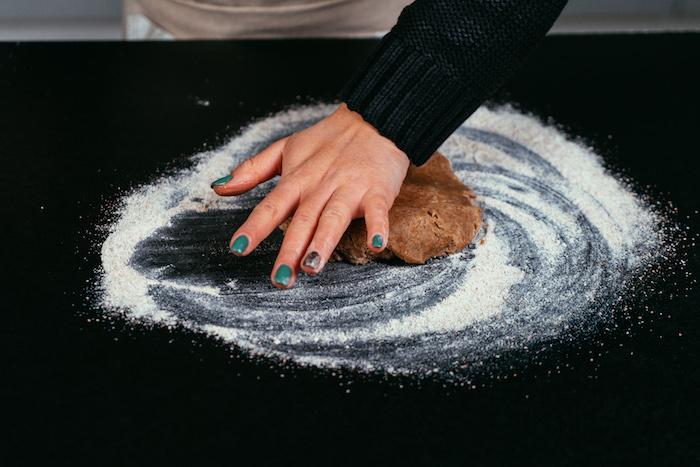 écraser la pâte de la paume de sa main pour faire un gateau aux pommes façon tarte sur une surface farinée