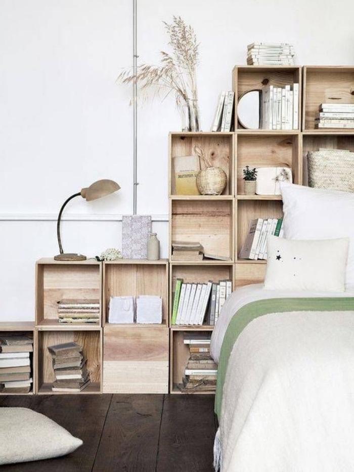 idée pour faire une tete de lit en caisses de bois, rangement livres et accessoires décoratifs derrière le lit, linge de lit blanc, parquet marron foncé