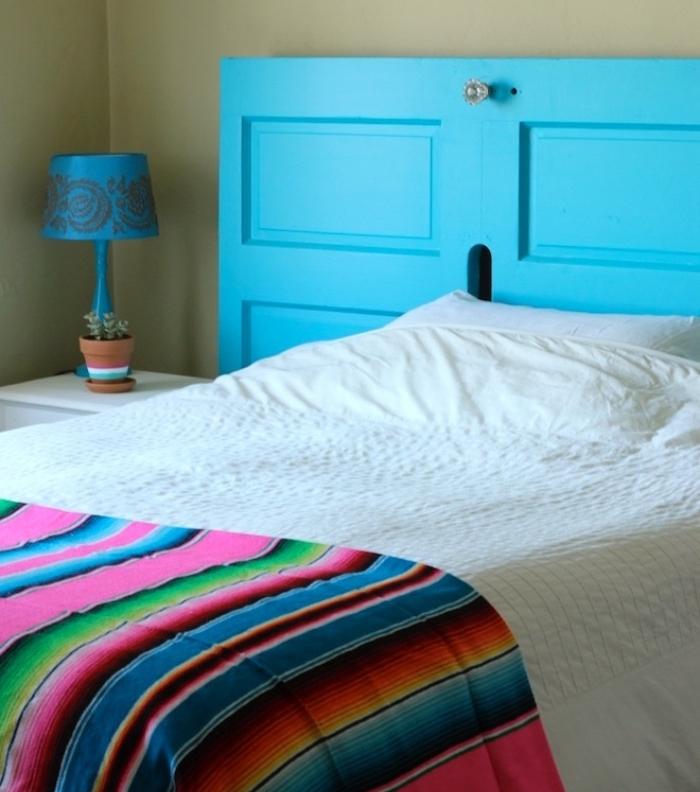 idée comment faire une tete de lit en vieille porte, repeinte en bleu, linge de lit blanc et couverture multicolore à rayures
