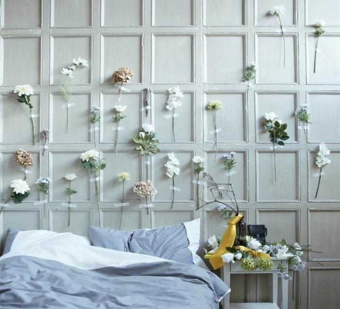 tete de lit a faire soi meme, des fleurs attachés au mur derrière le lit, linge de lit gris et blanc, diy deco chambre florale