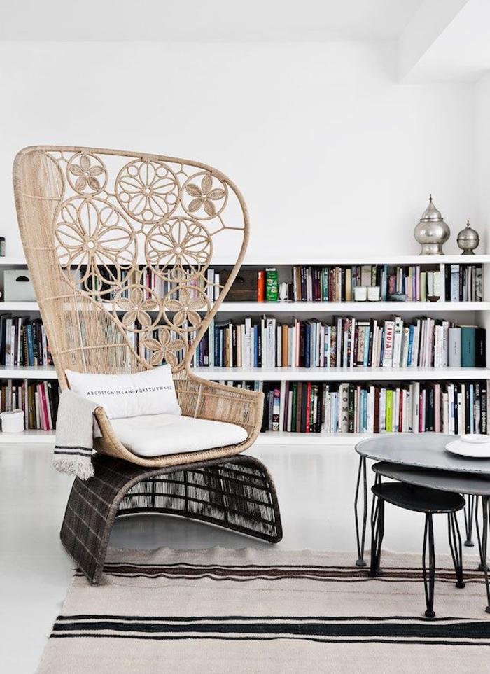 un fauteuil en rotin à dossier imposant, salon qui associe la déco scandinave et l'influence ethnique