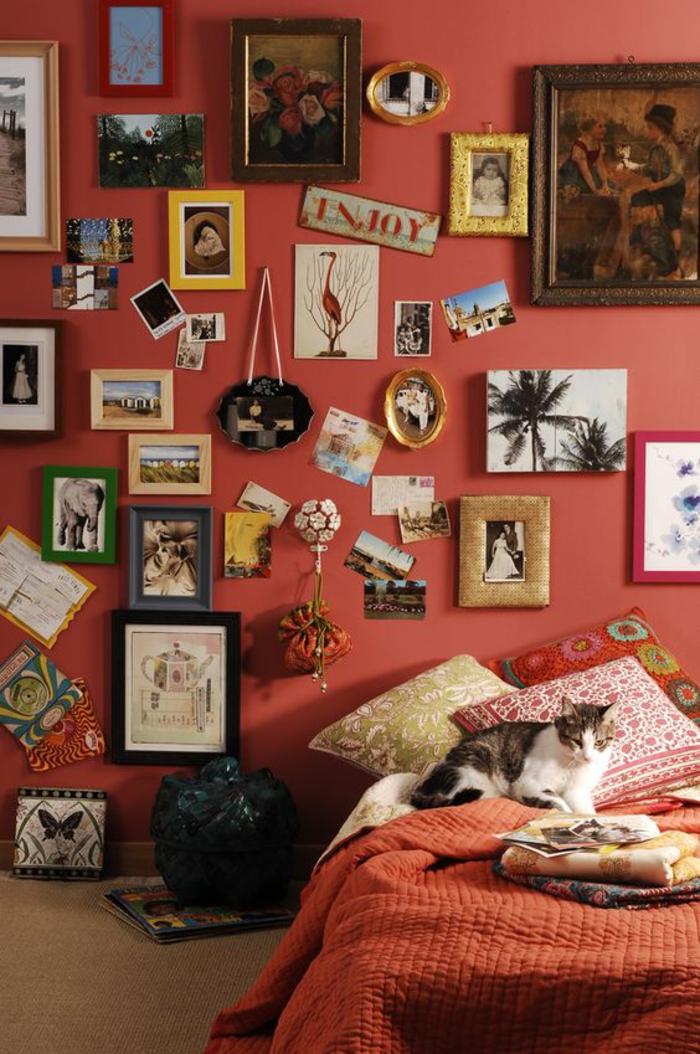 une chambre à couche éclectique de style bohème chic aux nuances de rouge et de terre sienne, un mur en cadres artistique