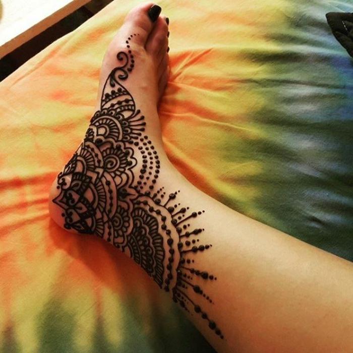 henné pied, fleurs et soleil sur la plante du pied, décoration traditionelle pour les pieds