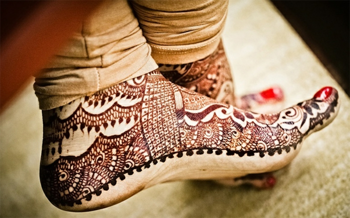 henné pied, dessin au henné fait avec une aiguille à dessiner, vernis rouge