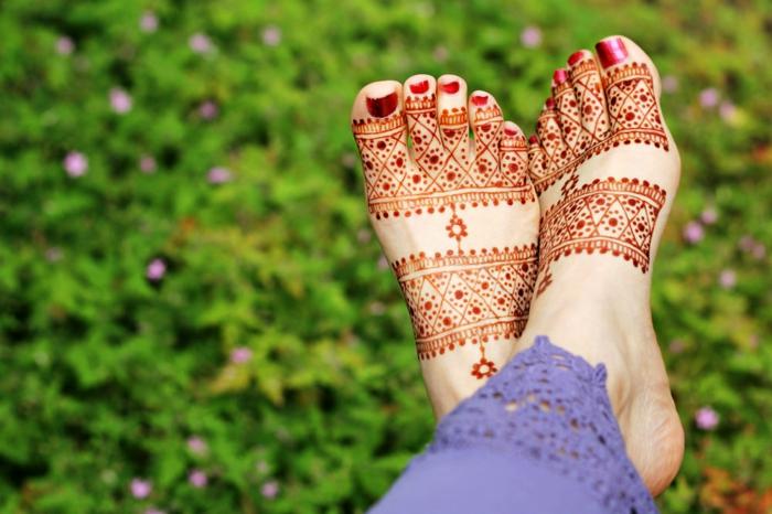 henné pied, dessin énergétisant de tatouage fait sur les pieds en couleur orange