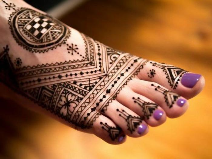 henné pied, motifs aztèques sur le pied et vernis à ongle lilas, figures géométriques