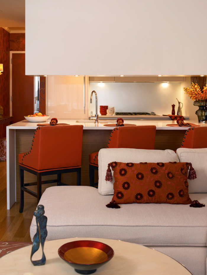 un îlot de cuisine en blanc immaculé aux accents déco colorés, tabourets de bar tapissés en terre de sienn