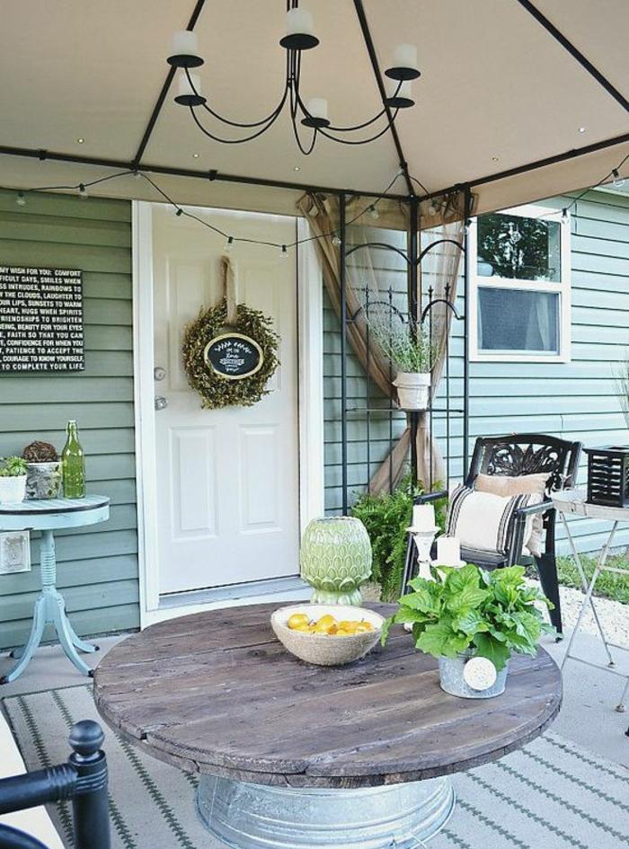 amenagement terrasse, deco touret, table plateau en bois, et pied en bassine de zinc, tapis gris, mobilier exterieur vintage, lustre retro