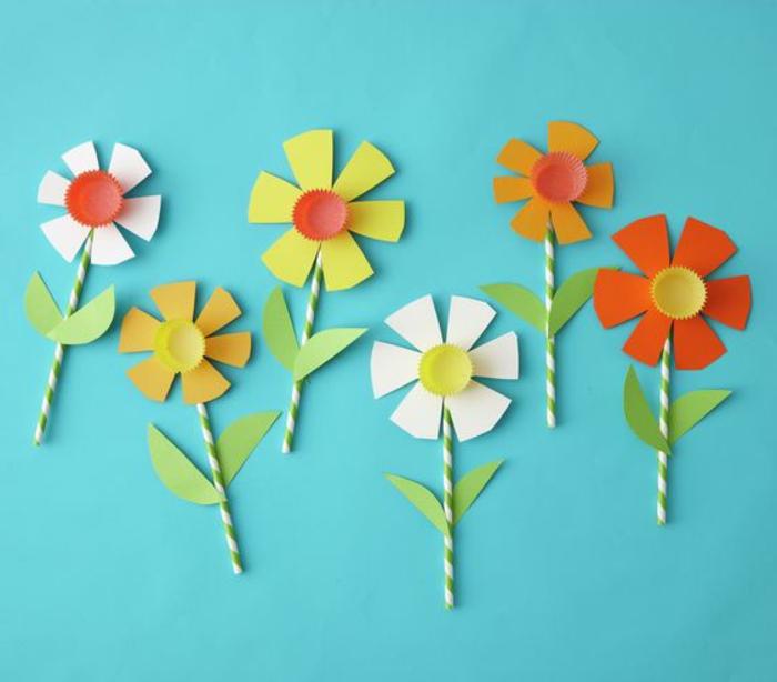 des fleurs en tige de paille, pétales et feuilles en papier et centre de couvercle de bouteille, activité manuelle primaire