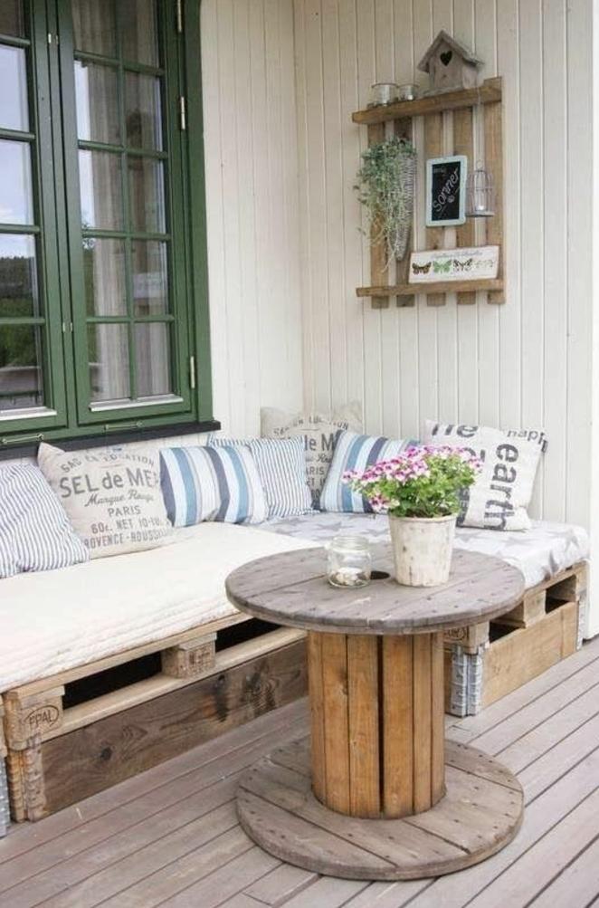 amenagement terrasse, deco exterieur, table basse touret, pot de fleur decoratif et canapé en palette, coussins multicolores, etagère en palette