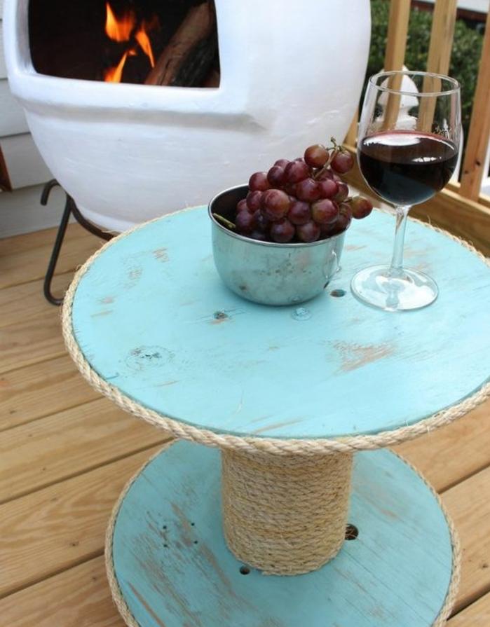 exemple de touret table basse patinée, couleur bleu clair et de la corde enroulée autour, dexo exterieur, amenagement terrasse, cheminée extérieure