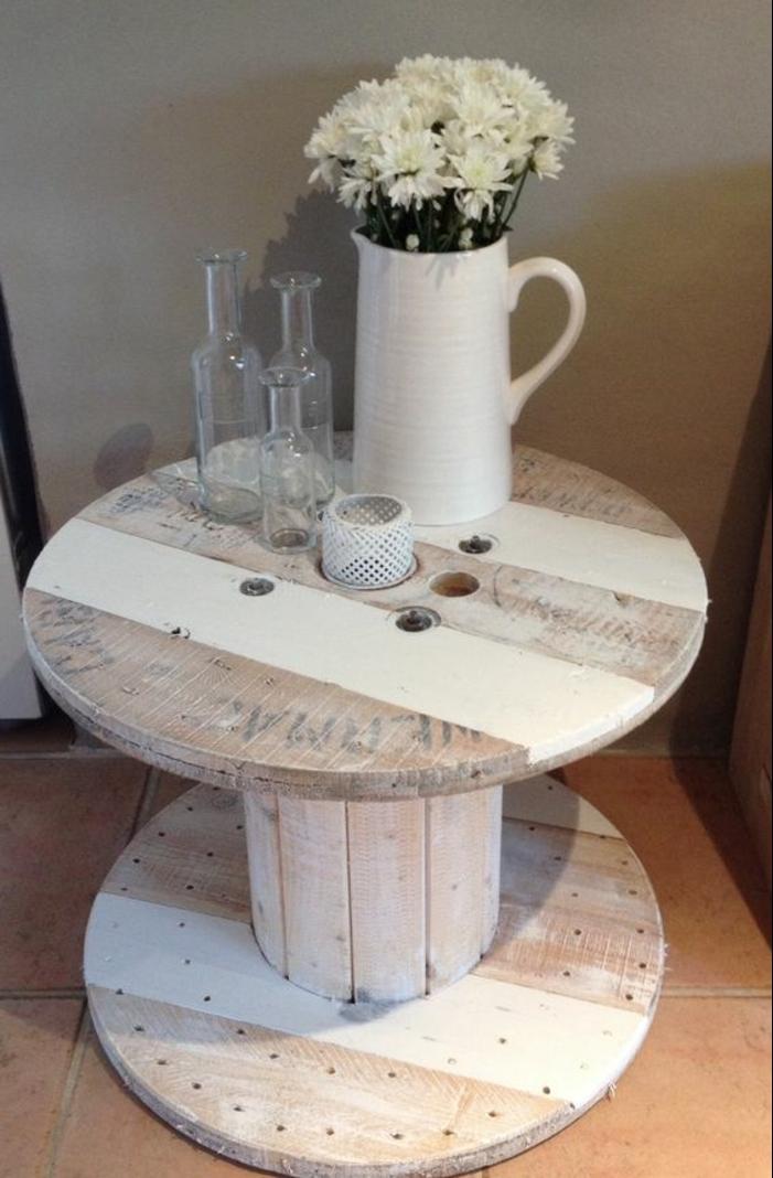 decoration salon campagne chic, table en touret en bois et rayures peinture blanche, bouquet de fleurs blanches dans un vase, bouteilles en verre decoratives