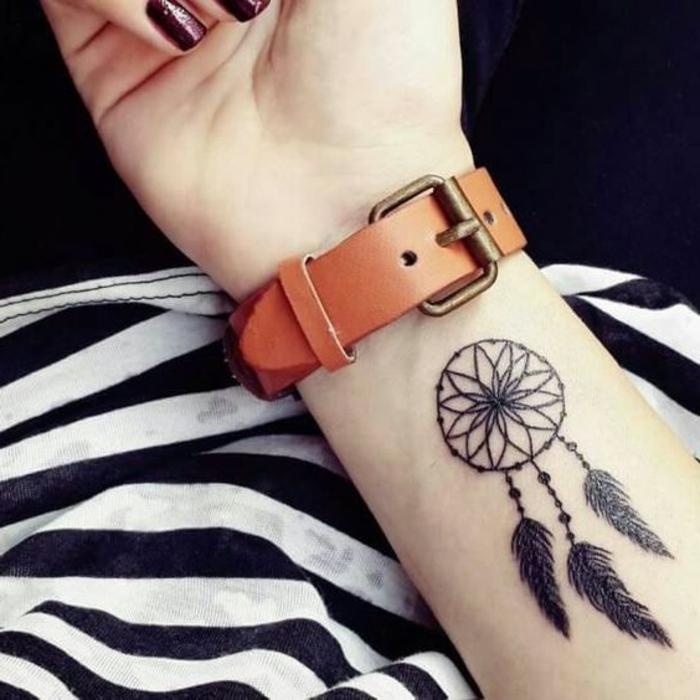 tatouage attrape reve avant bras graphique, encre noir, rosace, plumes, perles, une montre marron, comment se tatouer idée femme
