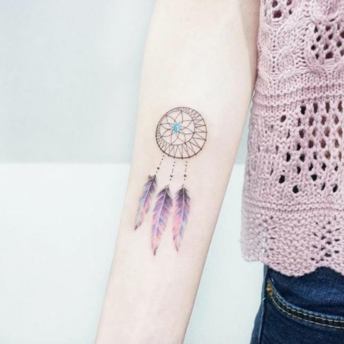 idée tatouage attrape reve avant bras, cerceau et filet noir, perle belue, plumes noir, bleu, mauve orange,