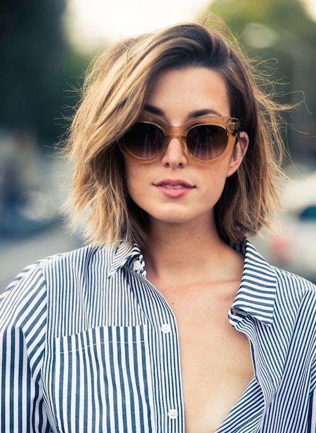 coiffure courte avec de legeres ondulations floues, chemise femme à rayures, lunettes de soleil