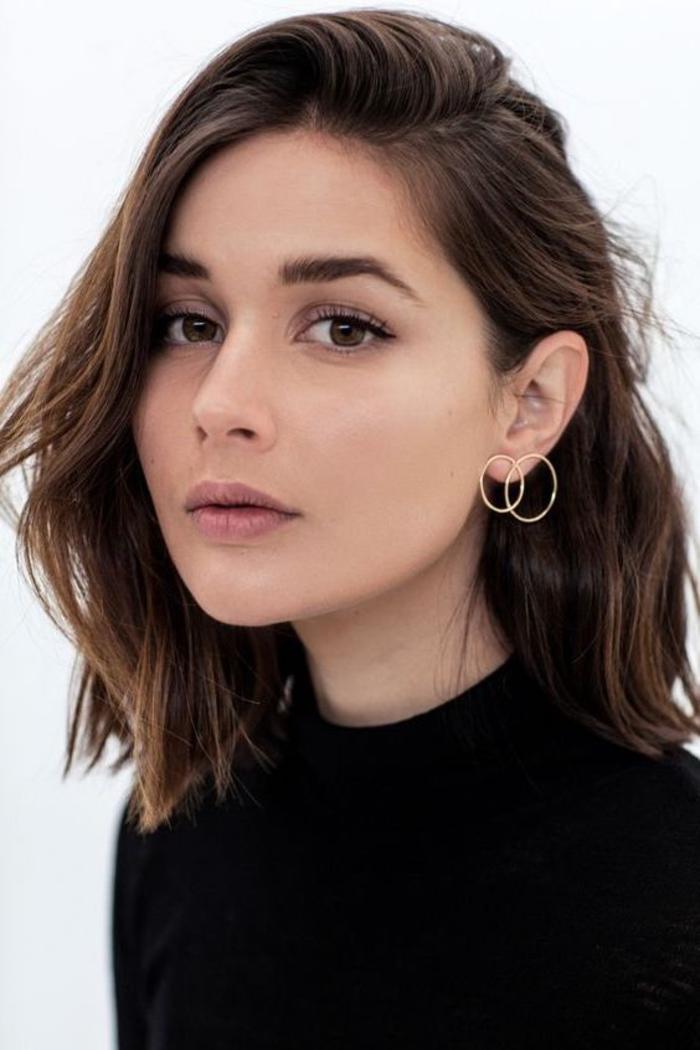 coupe femme courte, cheveux chatain foncé avec frange asymétrique, légères ondulations, boucles d oreilles rondes