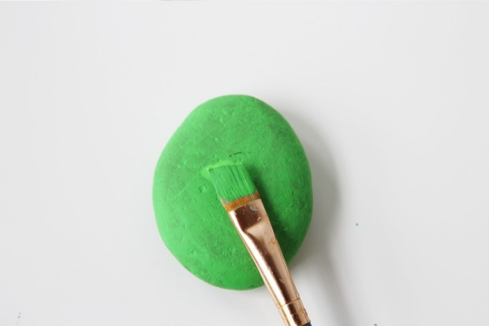 idée comment réaliser des galets décorés, galet repeint en vert à l aide d un pinceau, bricolage enfant, activité manuelle primaire