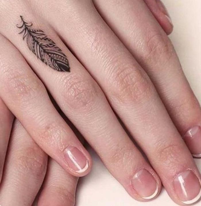 tatouage petit sur le doigt, phalange, plume, motifs tribal amérindiens, idée de tatouage femme créative