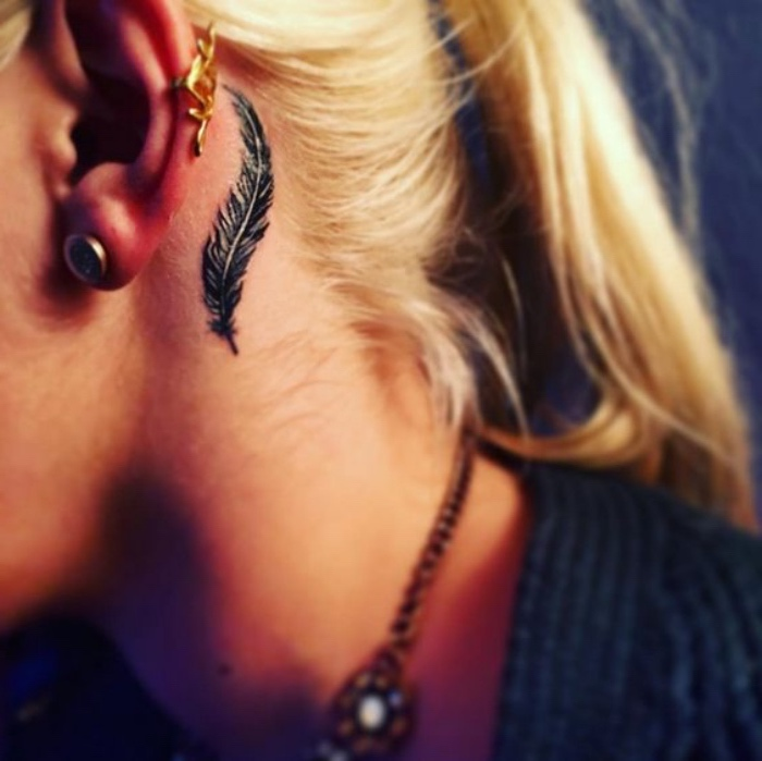idée de petit tatouage femme, derrière oreille, une plume noire, femme blonde, tattoo élégant