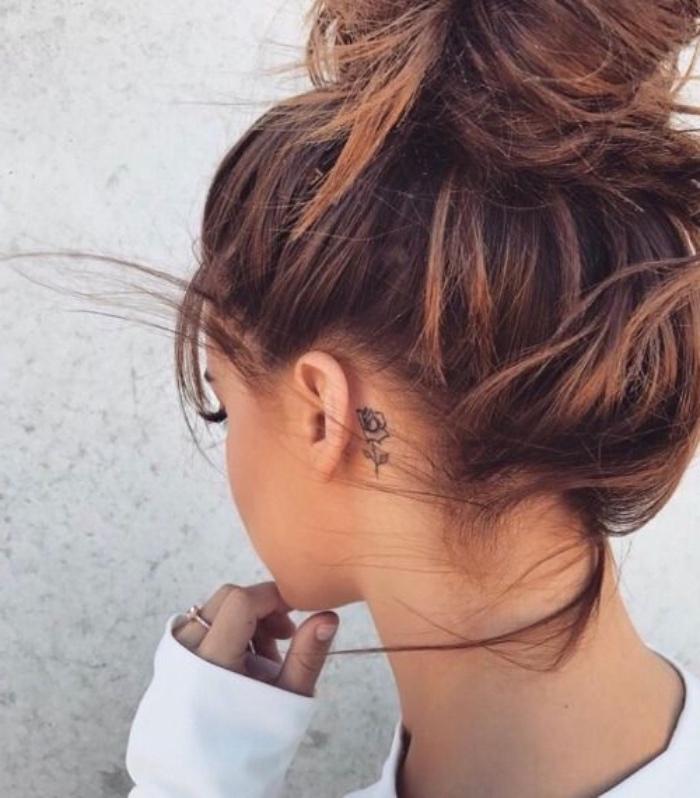 petit tatouage femme oreille, rose aux contours noirs, chignon décoiffé, fille brune, tattoo élegant