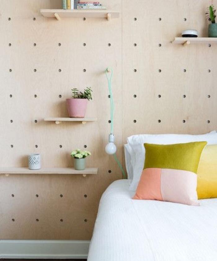 faire une tete de lit en panneau perforé avec des étagères rangement plantes et livres, coussins colorés et linge de lit blanc