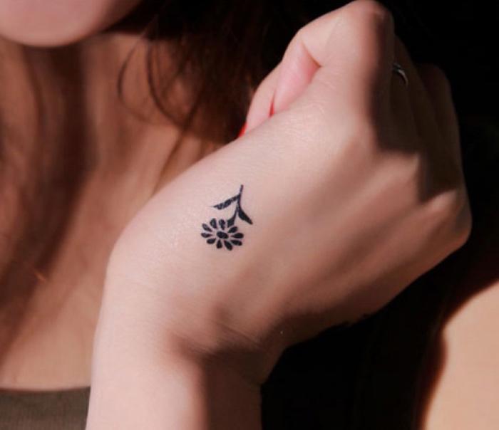 idée de tatouage petit femme main, une fleur noire, modele de tatouage minimaliste par excellence