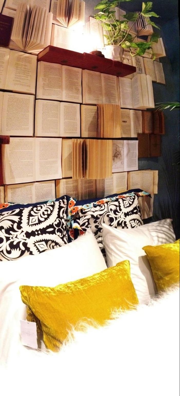 encore une idée pour fabriquer une tete de lit en livres ouverts, coussins motif azteque et coussins jaunes et blancs, couverture de lit blanche, lampe sur une étagère