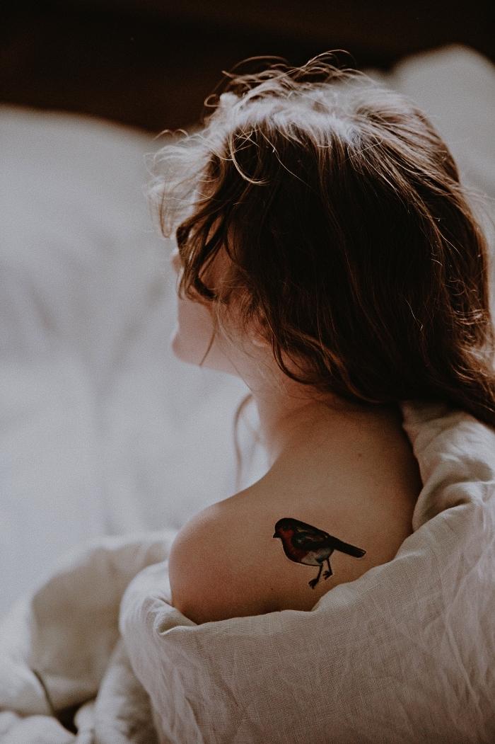 modèle de tatouage oiseau femme coloré sur le dos, tatouage d'oiseau chanteur dessin coloré et réaliste