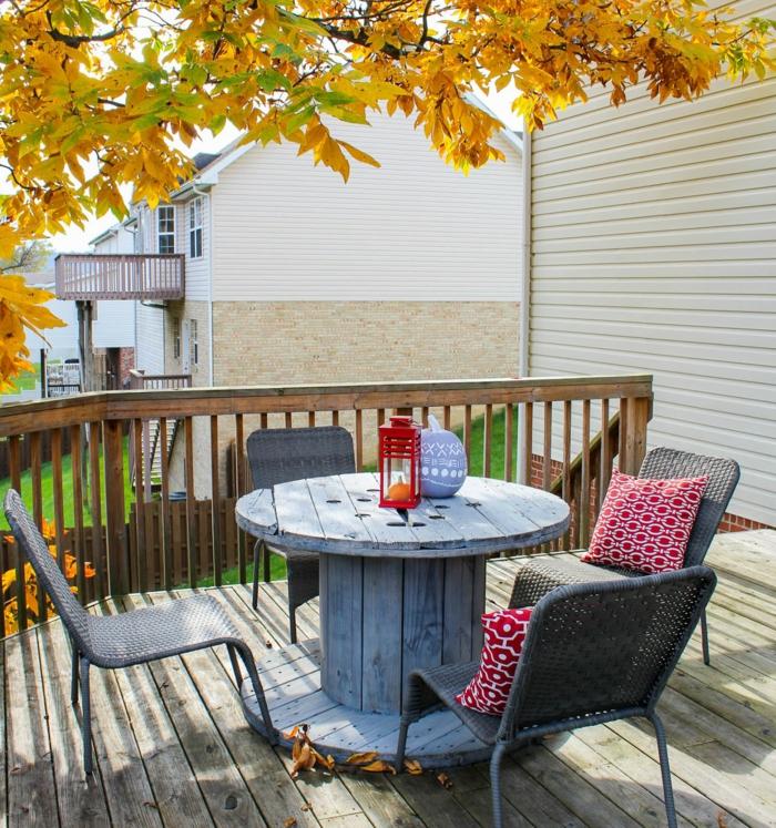 amenagement terrasse en bois de teck, table en touret repeinte en gris, chaises en rotin, paysage automnal