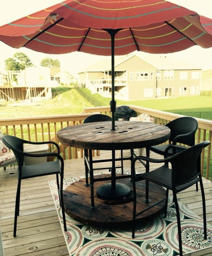 amenagement terrasse en teck, touret bois table vintage, un parasol qui passe par le centre, chaises noires, tapis à motifs orientaux