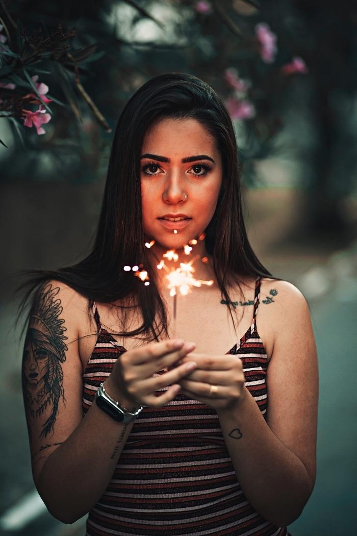 tatouage femme amérindienne à coiffe de plumes sur le bras accompagné de quelques tattoos phrase sur l'avant-bras et la clavicule, modele tatouage inspiré de la culture amérindienne