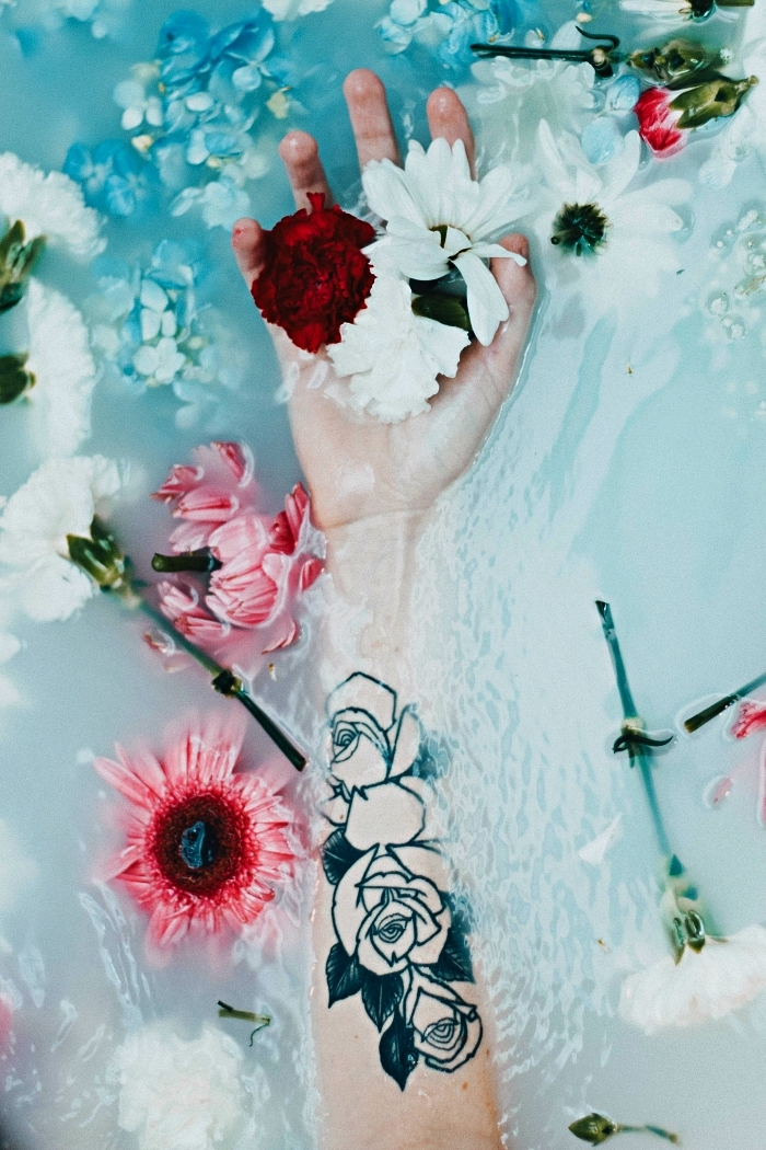 tatouage avant bras femme composé de trois roses à dessin graphique, idée de tatouage féminine à l'intérieur de l'avant-bras