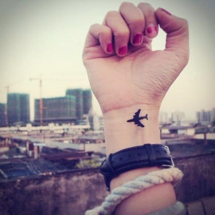 petit tatouage poignet, un avion encre noire, idée de tatouage voyage femme