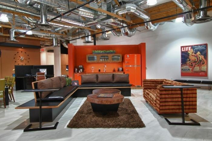 meuble noir et bois, pipes apparents, cuisine orange, horloge, fauteuil vert, canapé noir, table en bois, tapis moelleux