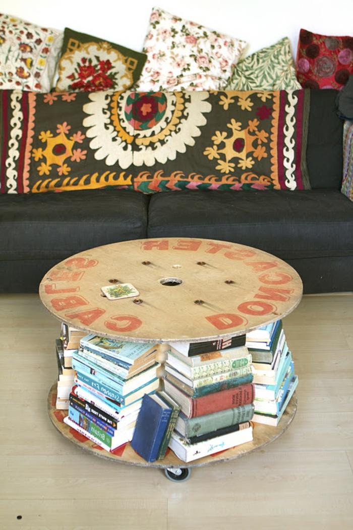 table basse touret à roulettes, rangement pour livres, canapé noir et coussins multicolores, motifs floraux et orientaux