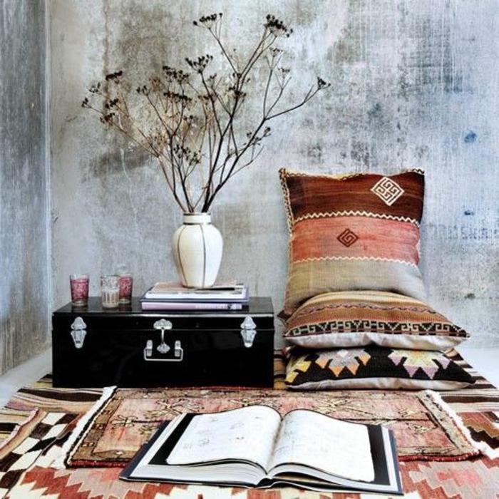 tissu ethnique, coussins aux motifs géométriques, enduit gris, vase avec fleurs sèches