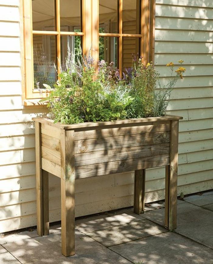 idée de bricolage bac a fleur en palette à pieds, des plantes vertes plantées dans une jardiniere placée à l extérieur, adossée à une maison