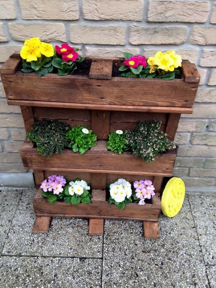 exemple de jardiniere en palette à trois niveaux, trois bacs a fleurs, pots de fleurs colorés, mur en briques, deco jardin exterieur