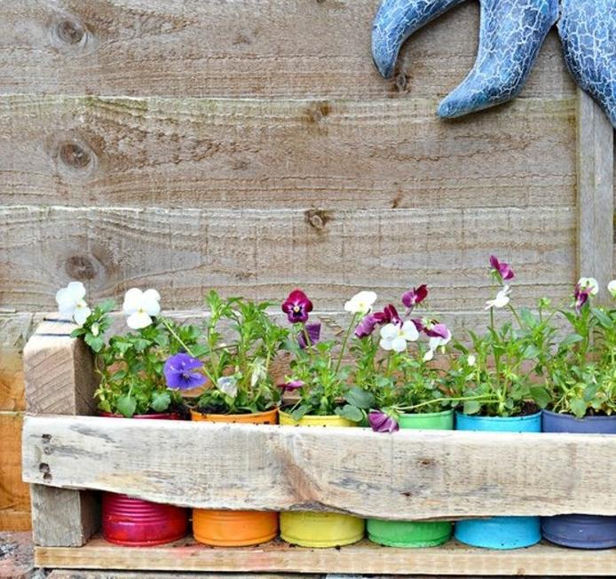 idée de jardiniere palette, en planches de bois brut, des boites de conserve repeintes, colorées et diverses fleurs plantées dedans