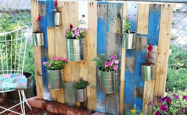 mur vegetal exterieur de palettes de bois, des boites en metal accrochées dessus, plantes fleurs rose, deco jardin à faire soi meme