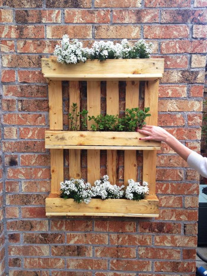 jardiniere en palette murale, des plantes blanches rangées à trois niveaux, contre un mur en briques exterieur